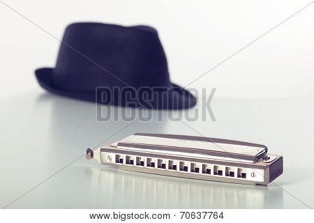 Still-life of hat and harmonica on white background