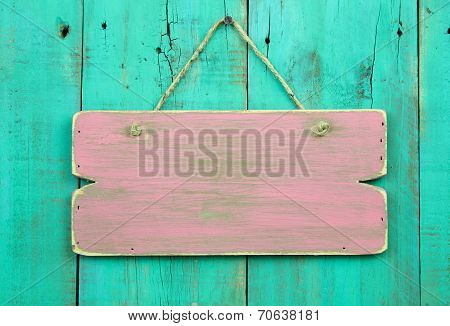 Distressed pink blank sign hanging on antique green wooden door