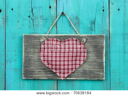 Distressed sign with large red checkered heart hanging by rope on antique teal blue wood door