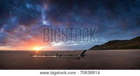 Landscape Image Of Shipwreck On Beach At Summer Sunset