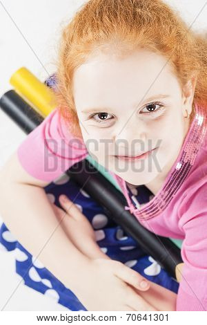 Cute And Happy Red-haired Caucasain Girl Holding Long And Big Pencils