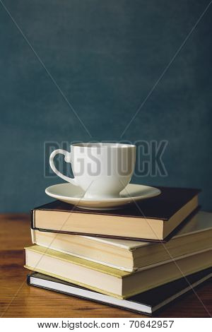 Coffee cup and stack of books