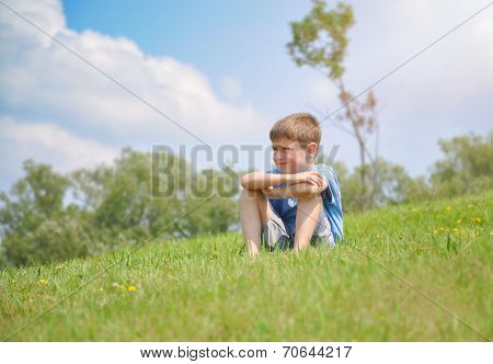 Boy Sitting On Green Nature Hill Outside