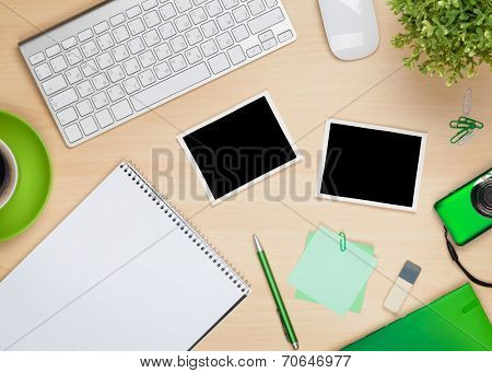 Photo frames on office table with notepad, computer and camera. View from above