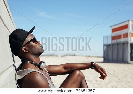 Relaxed African Man Leaning To A Wall At Beach