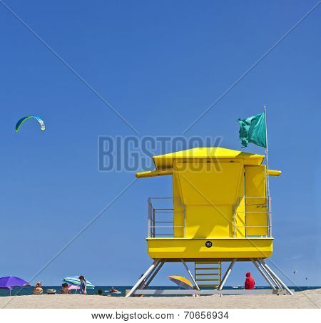 Yellow Life Guard Tower At The Beach With People, Kite Surfer And Blue Sky