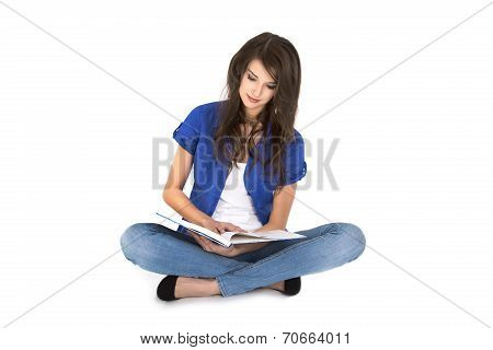 Isolated Young Woman With Open Book In Her Hands Sitting In Crossed Legs On The Ground.