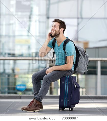 Man Relaxing At Airport And Talking On Mobile Phone