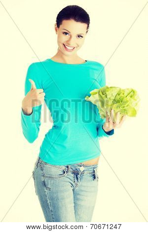 Portrait of attractive caucasian smiling woman with salat gesturing thumbs up, isolated on white