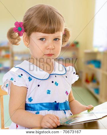 Girl reading a book while sitting at table.