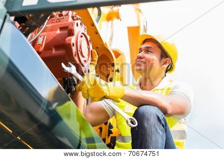 Asian engine mechanic engineer doing maintenance on machine