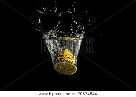 Halved Fresh Lemon Splashing Into Clean Water