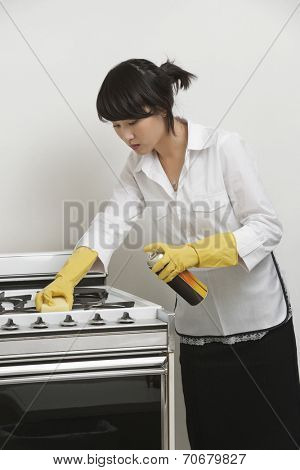 Young maidservant cleaning stove against gray background