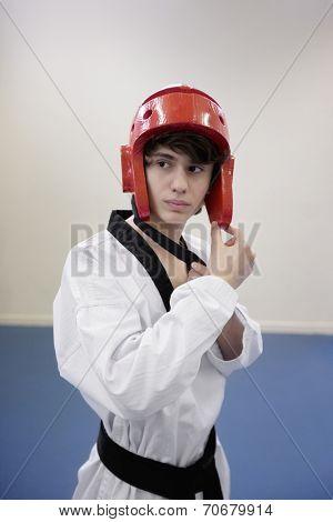 Teenage boy wearing martial arts headgear while looking away