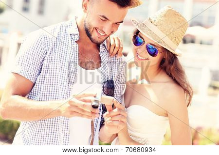 A picture of a young couple checking pictures on the camera