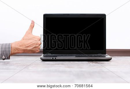 Closeup portrait of a male hand showing thumb up near the laptop