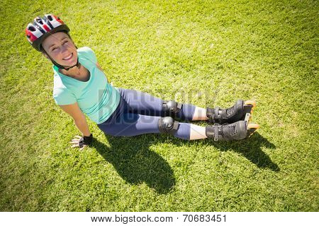 Fit mature woman in roller blades on the grass on a sunny day