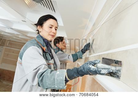 Plasterer at indoor wall renovation stucco decoration with float and plaster