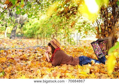 Woman lying on her stomach on autumn leaves in park, side view.