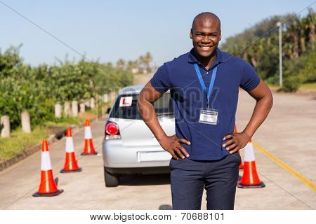 happy african driving instructor standing in testing ground