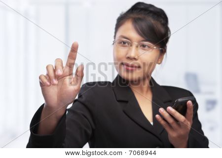 Asian Businesswoman Pointing Or Touching Blank Glass Screen