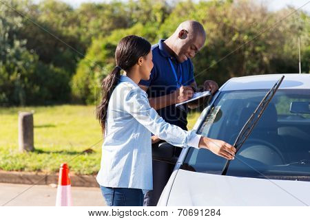 female african learner driver checking windscreen wiper during a driving test