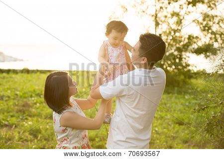 Happy Asian family playing in meadow during summer sunset, outdoors shot.