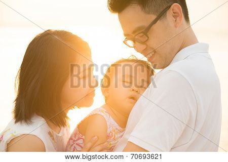 Portrait of happy Asian family outdoor beach vacation, during summer sunset, natural sunlight with flare.