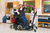 picture of wheelchair  - Spastic young man with infantile cerebral palsy caused by birth complications using a patient lift to maneuver himself into a multifunctional wheelchair for mobility - JPG