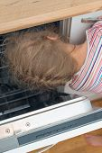 pic of dangerous situation  - Little girl putting head into dishwasher - JPG