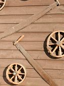 image of stagecoach  - Broken carriage wheels and rusty two man saws hanging on raw board wall - JPG