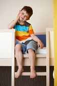 stock photo of bunk-bed  - Happy little kid sitting on bunk bed - JPG