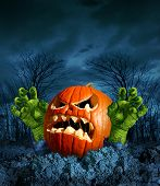 stock photo of jack o lanterns  - Zombie pumpkin halloween greeting card with copyspace as a scary surprise creepy jack o lantern with monster green hands rising from the dead on a dark cold haunted autumn night - JPG