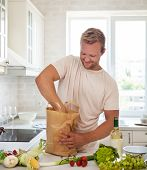 picture of reusable paper shopping bag  - Man holding paper bag full of groceries on the kitchen background - JPG