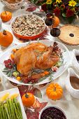 stock photo of kumquat  - Roasted turkey on a server tray garnished with fresh figs grape kumquat and herbs on fall harvest table - JPG