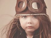 stock photo of goggles  - A little girl is wearing a pilot hat with goggles with an antique concept for career or imagination message - JPG