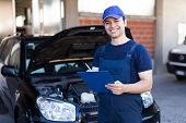 foto of clipboard  - Smiling mechanic writing on a clipboard - JPG