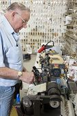 stock photo of locksmith  - Side view of locksmith working in key store - JPG