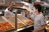 stock photo of pizza parlor  - Young guy buys a pizza in a modern restaurant - JPG