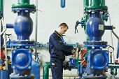 stock photo of pressure vessel  - repairman engineer of fire engineering system or heating system open the valve equipment in a boiler house - JPG