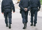foto of jumpsuits  - Three police walking in a street for city security - JPG