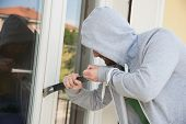 image of raid  - A criminal try to burgle and steal in a home - JPG