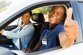 stock photo of driving school  - happy male african driving instructor in a car with learner driver giving thumb up - JPG