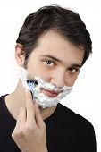 image of shaving  - portrait of a young man shaving himself with shaving foam on his face - JPG