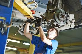 stock photo of suspension  - garage auto mechanic repairman checking car suspension during automobile maintenance at repair service station - JPG