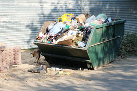 stock photo of dumpster  - Overfilled trash dumpster in ghetto neigborhood in Russia - JPG