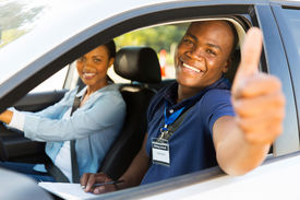 pic of driving school  - happy male african driving instructor in a car with learner driver giving thumb up - JPG