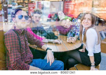 Group of young happy people enjoying and having fun (image taken behind glass reflection for desired look)