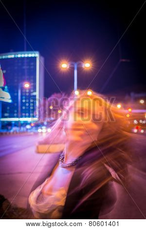 Girl walking on the night city street in slow motion (Note: this image is in motion, without still focus)