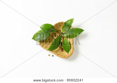 bowl of fresh bay leaves and peppercorns on white background